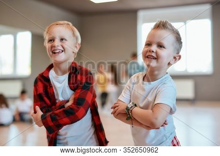 Cool Dancers. Two Fashionable Boys In Casual Clothes Keeping Arms Crossed And Smiling While Standing