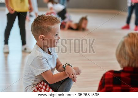 Portrait Of A Little Fashionable Boy Sitting On The Floor And Looking Away While Having A Choreograp