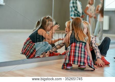 Back View Of Cute And Fashionable Little Girls Chatting While Sitting On The Floor In The Dance Stud