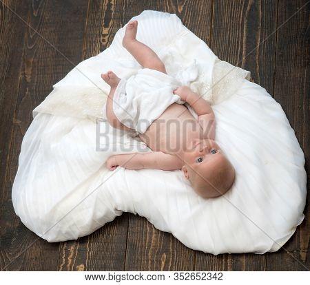 Baby Lying On White Soft Duvet Designed As Heart.
