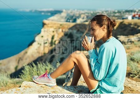 Carefree Young Woman Sitting On Cliff Edge, Drinking Coffee Or Tea, Enjoying Amazing Nature View Of