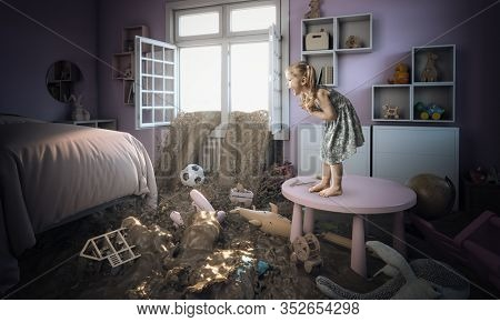 3-year-old Caucasian blond girl frightened and standing on a small table sees mud entering her bedroom. concept of disaster and family problem.