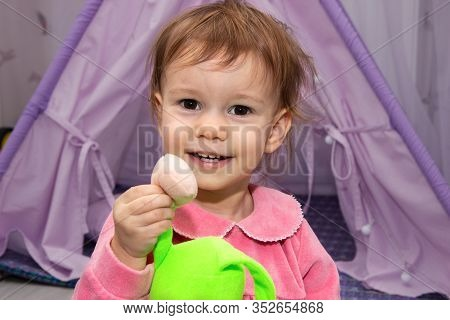 Little Girl 2 Years Old Smiling And Show Colorful Toys Near Wigwam In Childrens Room.