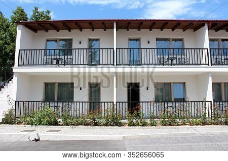 Front View Of Row Of Newly Built Motel Room Balconies With Black Metal Fences And Outdoor Furniture