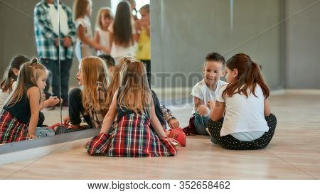 Back View Of Fashionable Kids Talking With Each Other While Sitting On The Floor And Having A Break