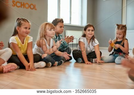 A Group Of Little Cute Girls And Boys Sitting On The Floor And Talking To Each Other In The Dance St