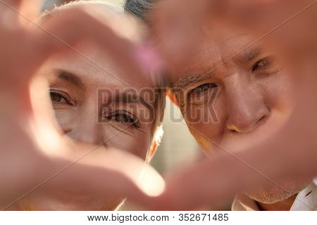 Close Up Photo Of Happy Senior Couple Making A Heart Shape With Their Hands And Fingers. Love And Fa