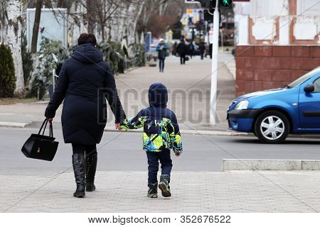 Woman And Kid Crossing The City Street Holding Hands. Mother Lead Little Boy, Concept Of Pedestrians