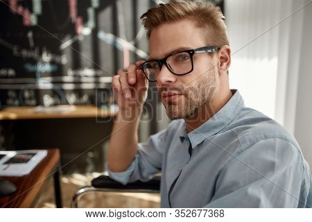 Young Confident Male Trader In A Wheelchair Looking At Camera And Adjusting Eyeglasses While Working