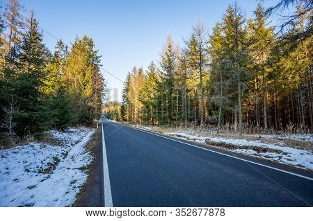 A Wet Roadway Where A Snow Storm Has Left Snow Even On The Bright Colored Leaves Still In The Trees