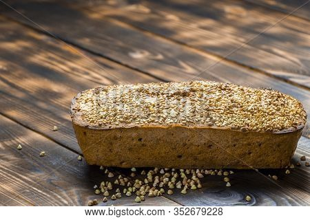 Gluten-free Buckwheat Bread With A Golden Brown Crust, Sprinkled With Sesame Seeds, Lies On A Wooden