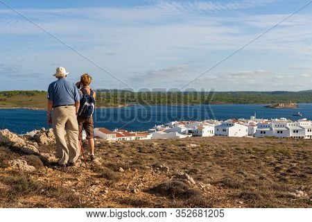Minorca, Spain - October 12, 2019: Tourists Looking At The Sea And The Beautiful Village Of Fornells