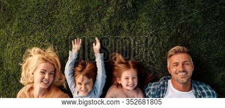 Top View Of Smiling Parents, Little Girl And Boy Having Fun While Lying On A Grass. Children, Family