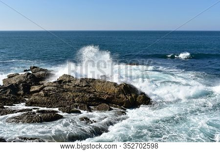 Seascape With Waves Breaking Against The Rocks And Blue Sky. Galicia, Spain.