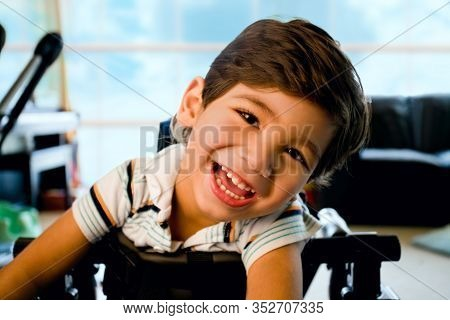 Disabled Little Boy Standing In Walker Smiling And Happily Looking At Camera With Bright Blue Sky An