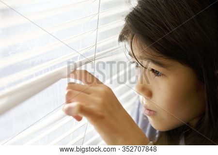 Biracial Asian Caucasian Girl Cautiously Peeking Out Window Through White Blinds, Looking Out