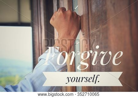 Inspirational Quote - Forgive Yourself. With An Emotional Gesture Of A Man Hand Clenched Fist On The