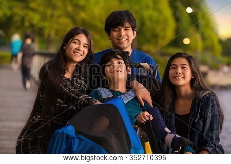 Older Siblings, Brother And Sisters, Surrounding Little Disabled Boy In Wheelchair Outdoors At Lake