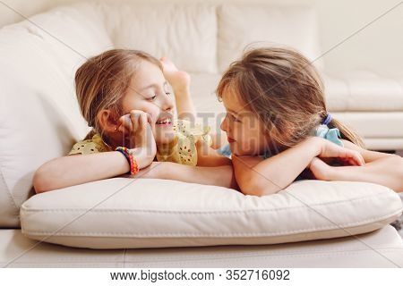 Two Cute Little Caucasian Girls Siblings Playing At Home. Adorable Smiling Children Kids Lying On Co