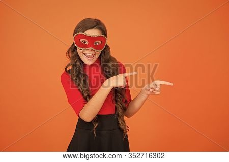 Holiday Sale. Happy Girl In Carnival Mask Pointing Index Fingers At Something. Small Child Smiling A