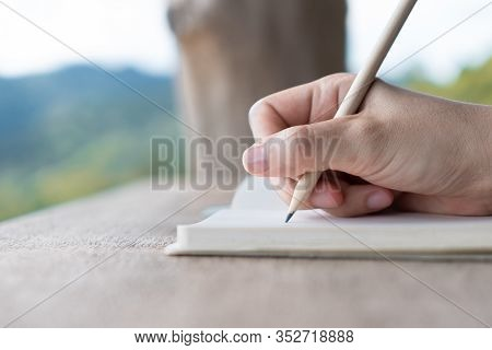 Woman Hand Writing Down In Small White Memo Notebook For Take A Note Not To Forget Or To Do List Pla