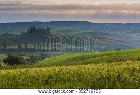 TUSCANY, ITALY - CIRCA MAY, 2017: Tuscany landscape at sunrise with farm house and hills, Italy