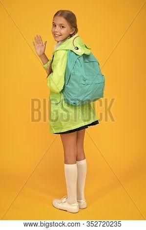 Rain Is Not Hindrance. Schoolgirl Raincoat Going To School Waving Hand. Waterproof Fabric For Your C