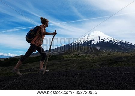 Young woman hiker walks on the deserted loose rocky trail on the mountain slope with snow capped volcano of Osorno on the background in Chile