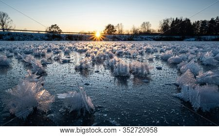 Pond covered with new ice with intricate frozen icy flakes