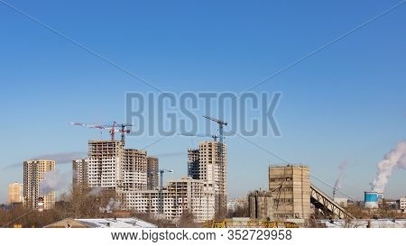 The Construction Of A Modern Multi-storey Residential Area, A Construction Crane Erects A Skyscraper