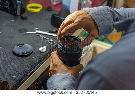 Closeup Photo Of Technician With Amputated Finger Cleaning Camera Lens