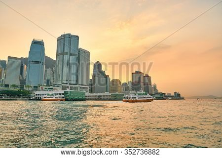 HONG KONG, CHINA - CIRCA JANUARY, 2019: view of the Central Ferry Piers with Central District in the background as seen from Victoria Harbour at twilight.