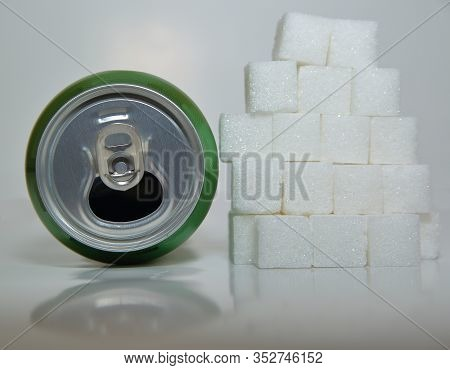 Open Can Reflecting In White Table Next To Lump Sugar Cubic Put One By On On Stack Close Up