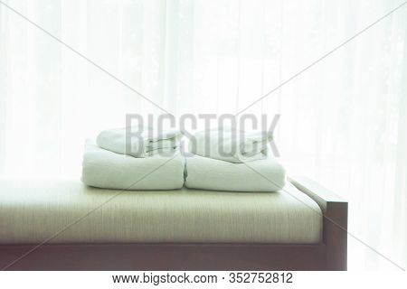 White Towels Were Laid On Sofa By The Window, With White Curtains In The Background.