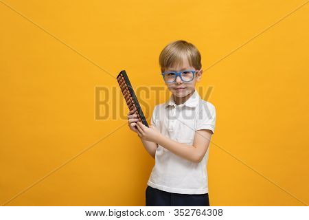 Cute Little School Boy In Glasses Holding Abacus On Yellow Background. Mental Arithmetic, Math, Math