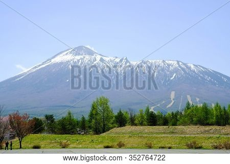 View Of Mount Hachimantai, With Green Pine Forest People Looking At The Mountain With Blue Sky In To