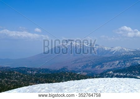 View Of Mount Hachimantai, With Green Pine Forest And White Snow Foreground With Blue Sky In Tohoku,