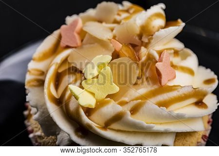 Closeup Of Cupcake Buttercream Topping Drizzled With Caramel And Colorful Butterfly Shaped Sprinkles