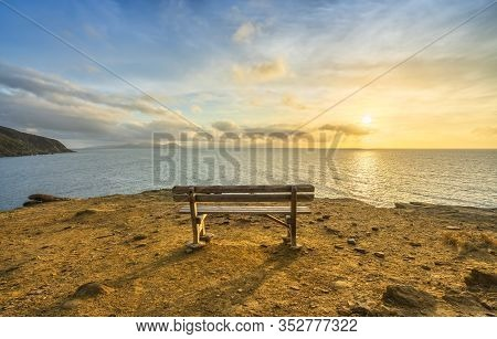 Bench In Populonia Famous Cliff Buca Delle Fate At Sunset. Elba Island On The Horizon. Piombino, Mar