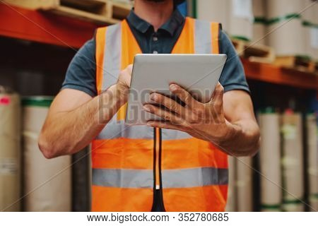 Close-up Of Warehouse Worker In Orange Vest Holding Digital Tablet Working While Checking On Invento