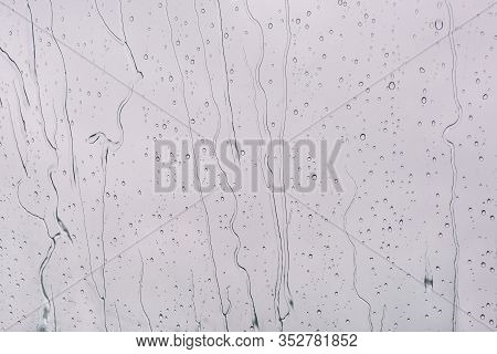 Raindrops Background. Flowing Water From The Surface Of The Window. Raindrops And Jets On A Gray Bac