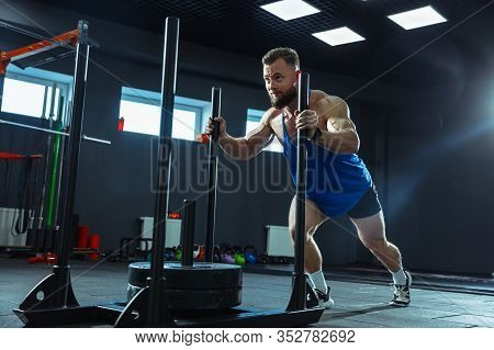 Young Muscular Caucasian Athlete Training In Gym, Doing Strength Exercises, Practicing, Work On His