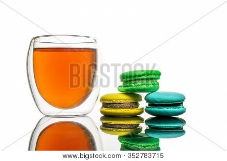 Colorful French Macarons Background With Glass Cup Of Black Tea, Close Up. Tasty Sweet Color Macaron