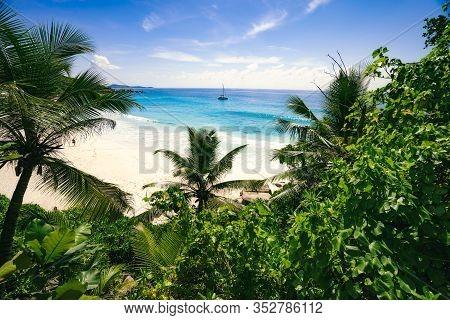 Petite Anse Paradise Beach Framed By Green Foliage. La Digue Island, Seychelles