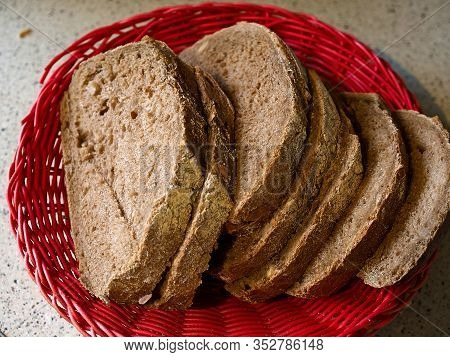 Whole Grain Country Style Black Bread Cut Into Slices Served In A Coutry Style Rustic Tray