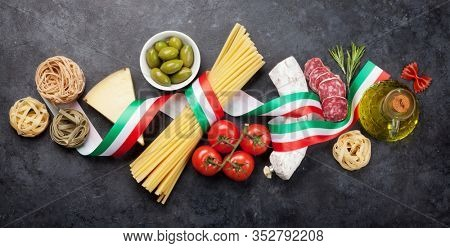 Italian cuisine food ingredients. Pasta, cheese, salami, olives and tomatoes. Top view flat lay on stone table