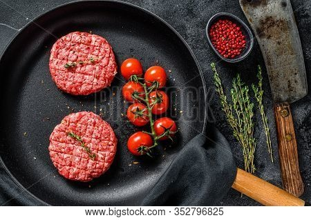 Raw Minced Beef Meat Cutlets, Patty In A Pan. Black Background. Top View
