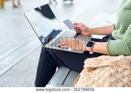 Young Asian Girls Holding Credit Card And Using Laptop Computer Shopping Online While Checking Fligh
