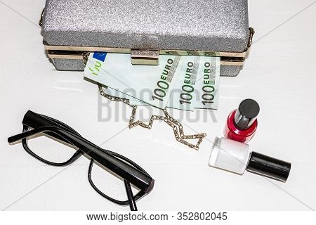 Glittery Silver Clutch Bag With Money And Beauty Products Isolated On White Background With Copy Spa
