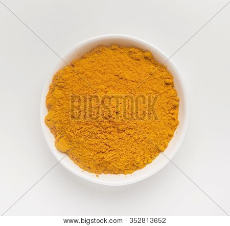 Closeup Turmeric Or Curcumin Powder In Bowl Isolated On White Background.top View. Flat Lay.
